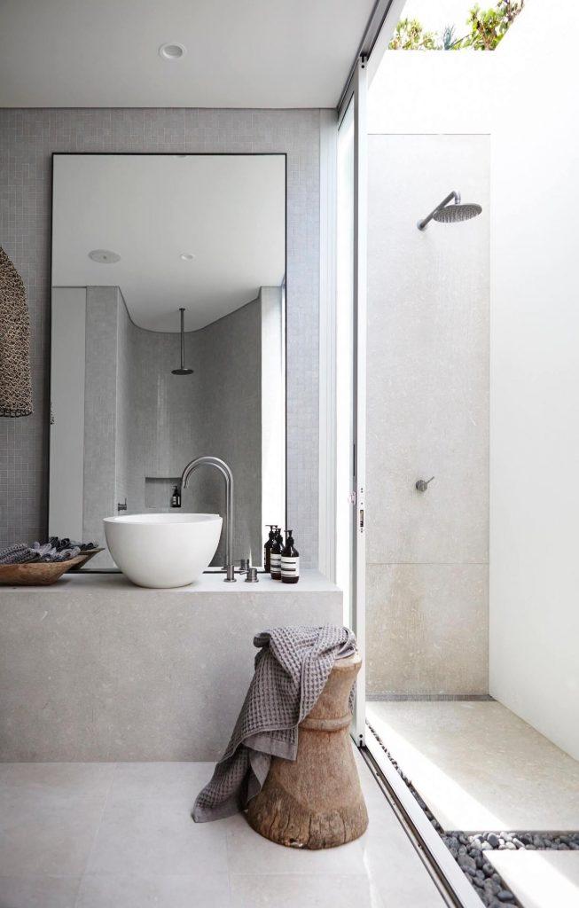specchio appoggiato al mobile lavabo di un bagno piccolo