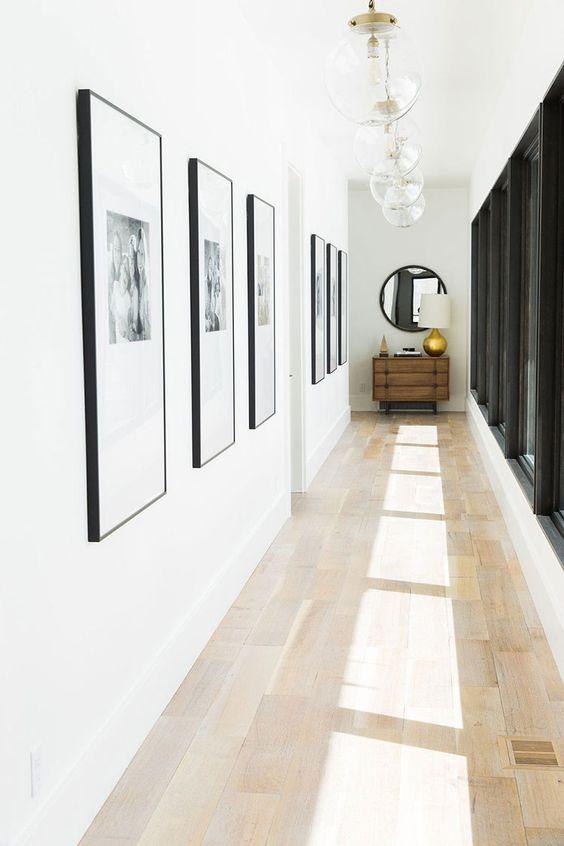 quadri uguali appesi in un corridoio con parete bianca