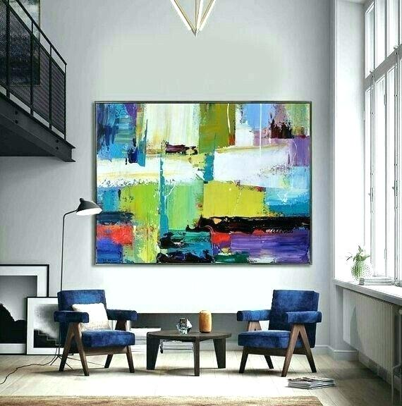 quadro grande astratto colorato appeso in salotto dietro due poltrone
