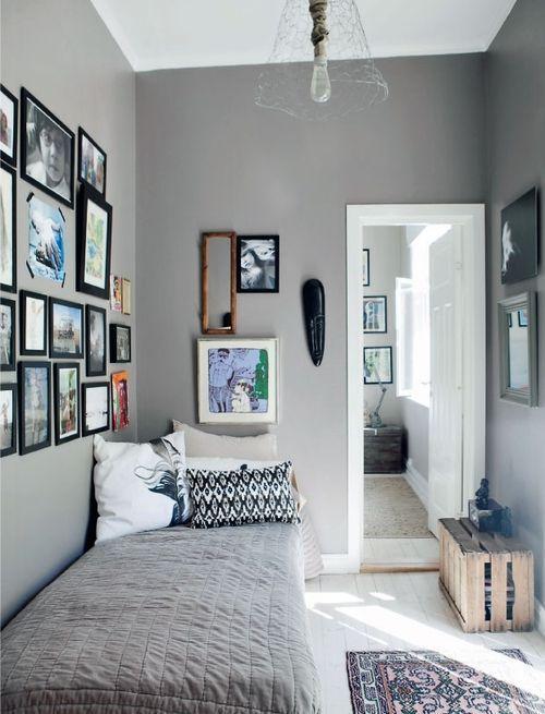 camera da letto con tanti quadri diversi appesi su parete grigia