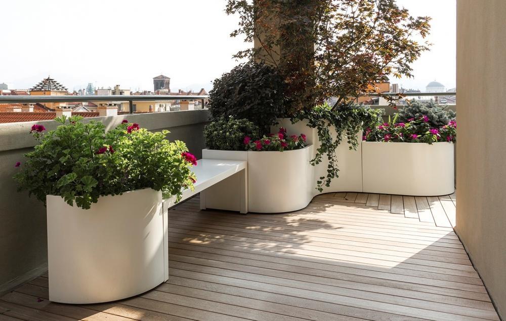 balcone grande arredato con panca, piante