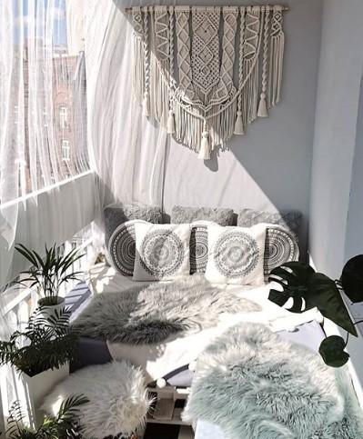 balcone arredato con divani cuscini tappeti