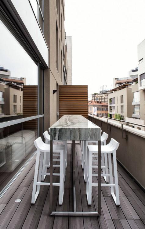 balcone lungo e stretto arredato con tavolo da bar e sgabelli